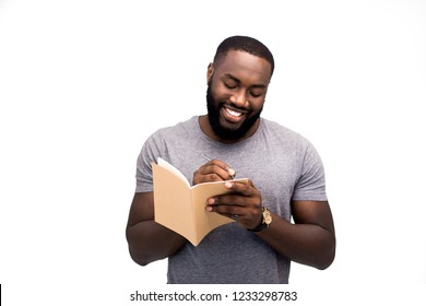 A romantic man writes a letter to his beloved girl with a pensive expression on his face, smiles, a declaration of love, shyness and timidity, important words and a romantic mood. Isolated