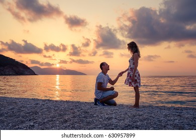 Romantic marriage proposal on the beach at the seaside at sunset over the sea. Young couple in love