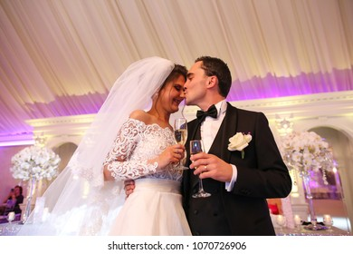 Romantic married couple bride and groom kissing at wedding reception
