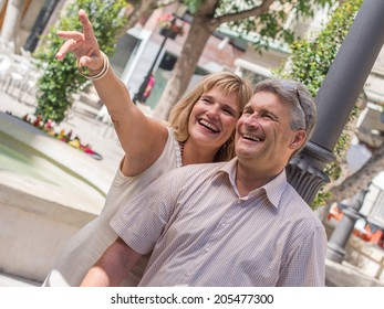 Romantic mature attractive couple pointing out something amusing to her husband as they stand close together in the summer sunshine sightseeing on their summer vacation to the tropics