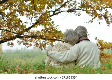 Romantic mature couple is sitting in the park in fall