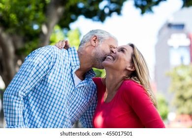 Romantic mature man kissing woman in city