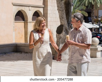 Romantic mature senior affectionate middle-aged couple enjoying an ice cream cone on a hot day as they walk along an urban street hand in hand smiling and chatting