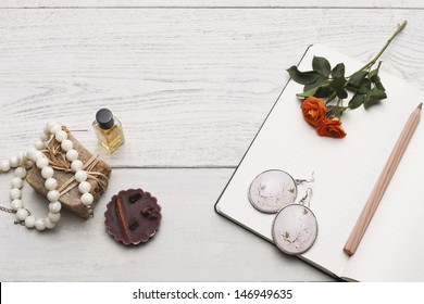 Romantic memories. Group of personal accessories and objects on white hardwood table. Studio shot