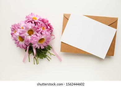 romantic message concept. a small bouquet of flowers and an envelope. space for text. flat lay. top view. invitation. congratulation. White background