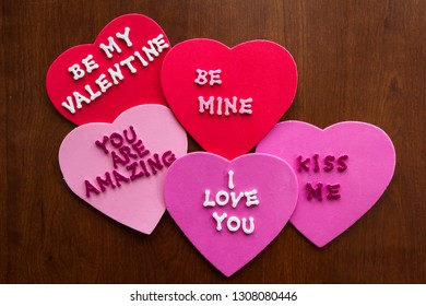 Romantic messages written with glitter letters on colorful hearts stuck on a wooden background