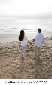 Romantic mid-adult Hispanic couple watching sunrise at beach