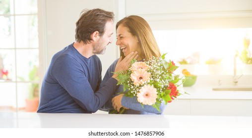 Romantic middle age couple holding flowers in love at home