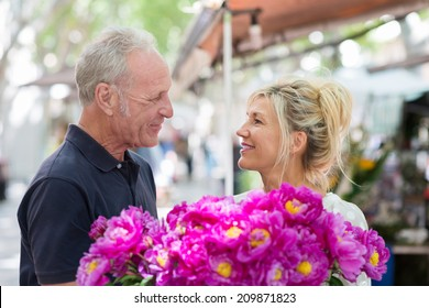Romantic middle-aged man giving his beautiful wife flowers presenting her with a huge bouquet of magenta colored blooms