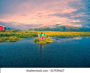 Romantic miniature scandinavian red house on tiny islet