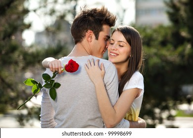 romantic moment: young man giving a rose to his girlfriend