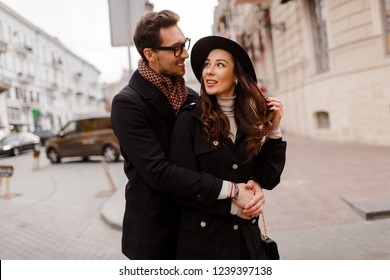 Romantic moments of  beautiful elegant couple in love walking in the city,  hugging and enjoying time together. Warm colors. Valentine. Perfect hairs and make up. Lifestyle.