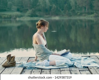 Romantic mood for evening reading a book on the pier. A young woman in a shirt, white trousers and bra sits on the pier, against the lake with the forest and reads a book.