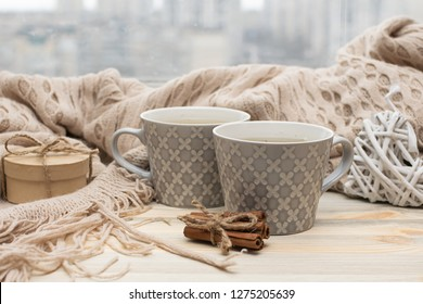 Romantic morning composition with two cups of green tea and warm blanket.  St. Valentine's Day background. Hygge home interior.