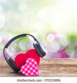 Romantic music concept  - two red and pink hearts with headphones with garden bokeh background
