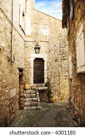 Romantic narrow cobble street with sandstone houses in a village of Saint Paul de Vence, France