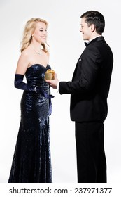 Romantic new year's eve fashion couple wearing black dinner jacket and dark blue dress. Man giving a present. Isolated against white.