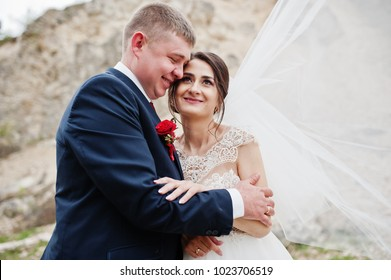 Romantic newly married couple posing and walking in rocky countryside on their wedding day.