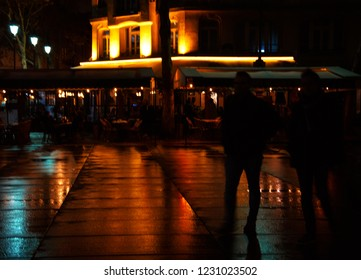 Romantic nightlife Paris at autumn. Blurry night view of Parisian square after rain. Colorful lights reflection on wet pavement. Silhouette of walking couple. People enjoying in cafe at background.