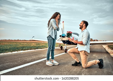 Romantic offer to get married. man makes offer to his girlfriend in airdrome. Valentine day. Proposal concept. Young man giving flower boquet for girlfriend in valentine day. Small airplane background