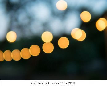 Romantic off-focused decorative outdoor Christmas string lights in the evening