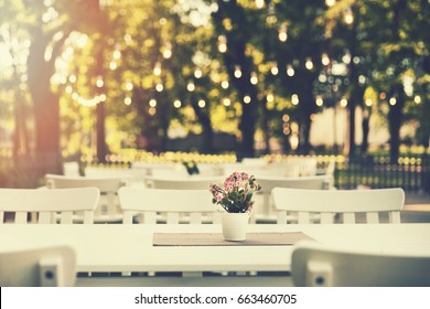 romantic outdoor restaurant in park with string lights at sunset