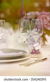 "Romantic outdoor wedding day concept - white tablecloth, white table setting, focused on ""your text here"" label, wild bouquet of flowers as a background"
