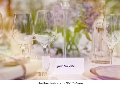 Romantic outdoor wedding in the old greenhouse- white tablecloth, empty glasses, white table setting, wild fresh flowers