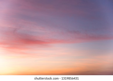 romantic pastel colored sunset sky in the evening with colorful clouds