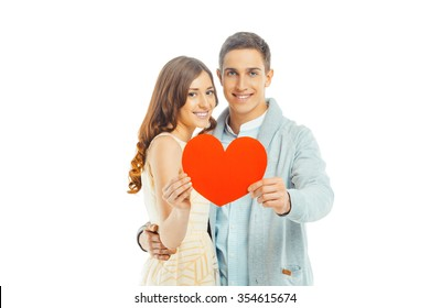 Romantic photo of beautiful couple on white background. Handsome young man and beautiful woman smiling, looking at camera and holding Valentine card in shape of heart