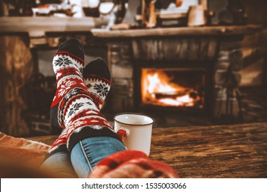 Romantic photo of home interior and woman legs with christmas socks. Free space for your decoration
