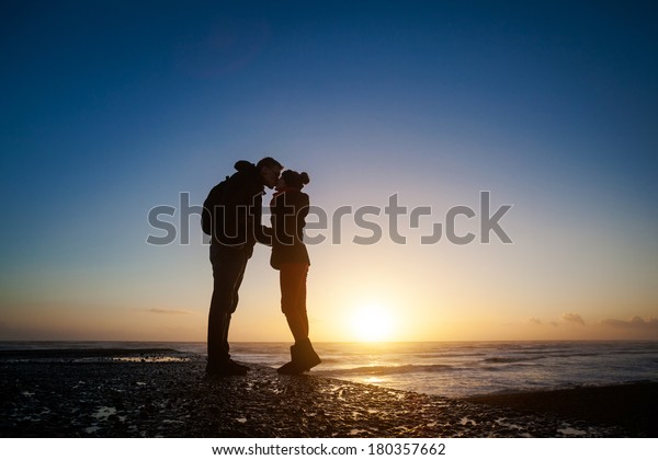 Romantic photo of kissing couple during sunset, made in Brighton, England