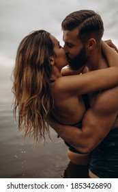 Romantic photo session in the water. A guy and a girl swim in the lake in the evening. Beautiful sunset. A passionate kiss.