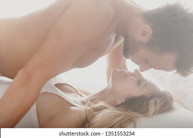Romantic photo of sexy pair kissing and caressing in bed