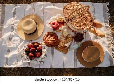 Romantic Picnic Food And Drink on Blanket Top View. Peaches Fruit and Cakes, Donuts and Croissants, Baguettes in Basket, Champaign Bottle and Glasses. Tasty Snacks and Hats. Relaxation for Couple