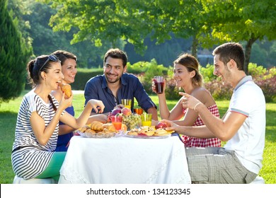 Romantic picnic. Group of five adult friends enjoying a healthy outdoor meal sitting together at a table in a lush green garden laughing and joking