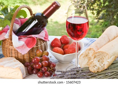Romantic picnic setting with wine, bread and cheese