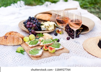 Romantic picnic with two wineglasses, delicious food, healthy fruits: avocado, grapes, figs. Straw hat, bag, sandwiches, croissants, cheese are on white plaid. Lunch in italian or french style