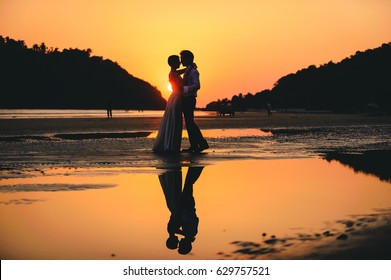 romantic picture of a couple in love, kissing and hugging each other in a charming exotic beach at sunset