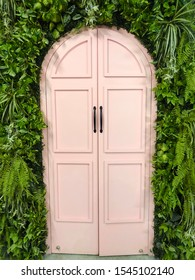 The romantic pink castle door with the green bush all around