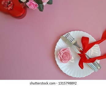 Romantic place setting. Plate, fork and knife with red bowknot, marzipan rose on pink background. Top view. Place for text.