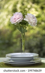 Romantic place setting with a tall elegant vase of fresh pink peonies served on a garden table against greenery for a Valentines or anniversary tryst