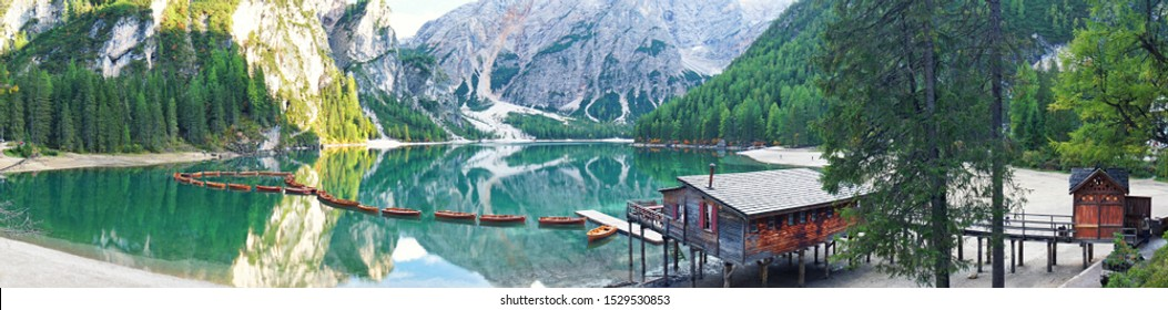 Romantic place with typical wooden boats on the alpine lake panorama