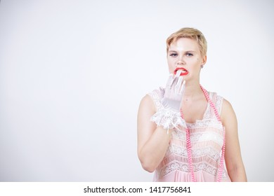 romantic plus size girl with short blonde hair in pink lace nightgown, white thin transparent gloves and pearl beads on white background in the Studio alone
