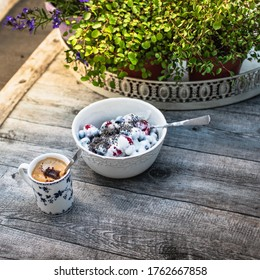 Romantic porcelain cup of coffee and a bowl with fresh raspberries, blueberries, yogurt and chia stands on a wooden table in the garden. against the background of plants and flowers.