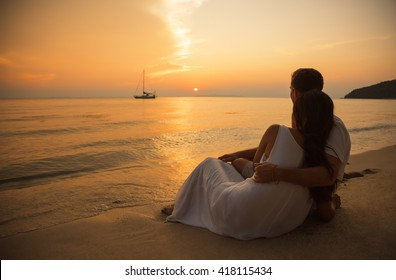 Romantic portrait of attractive couple in love hugs sitting on the beach at the sunset on  tropic island. Against the backdrop of the sea and setting sun. In the distance a boat in the sea. Silhouette