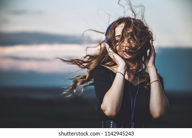 romantic portrait of a beautiful girl in headphones with flying hair from the wind, young woman listening to music on the nature in the field