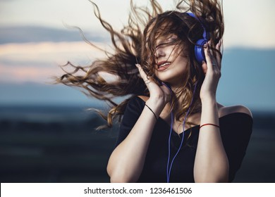 romantic portrait of a beautiful girl in headphones with flying hair from the wind, young woman listening to music on the nature in the field, concept teenager lifestyle