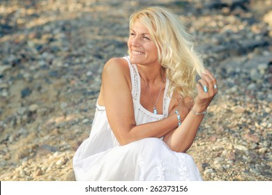 romantic portrait of a beautiful older woman. Mature beautiful blonde in a white dress walks on the  road