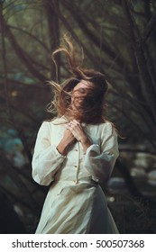 Romantic portrait of beautiful woman with blowing hair. Surreal forest